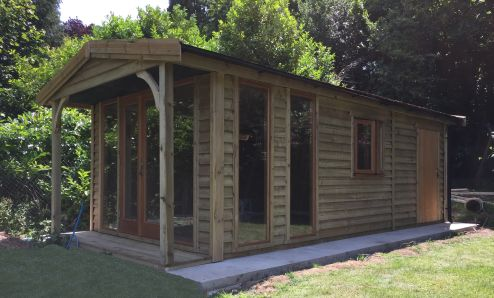 Clad in Feather Edge and with a <br.>traditional style roof and contemporary doors,