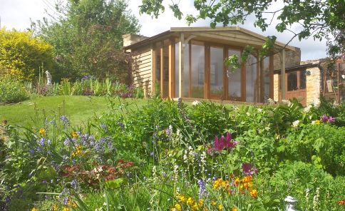 A traditional style 3.8m x 2.4m Garden Office or Garden Room with a pitched roof and featuring contemporary glazing options. The front overhang provides a covered seating area from which to enjoy views across the garden.