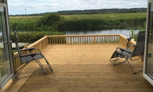 A Cedral Weatherboard Garden Room with sliding doors and decking makes it possible to enjoy this idyllic view over